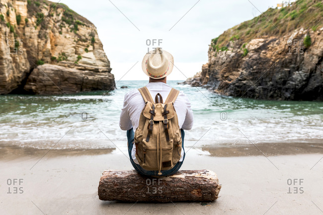Back view of unrecognizable male backpacker in hat sitting on wooden log on coast near sea with rocky cliffs and relaxing during summer journey