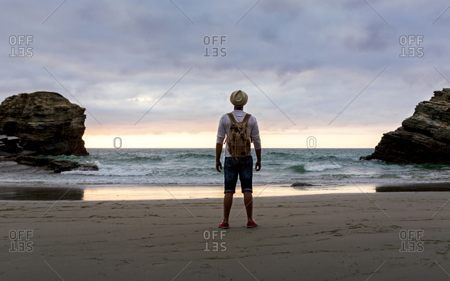 Full body back view of unrecognizable man with backpack standing on empty sandy shore against waving sea and cloudy sky and enjoying fresh breeze and freedom in summer evening during sunset