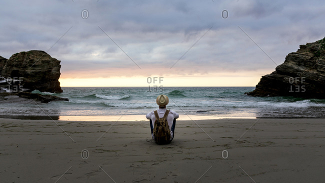 Back view of anonymous male traveler sitting on sandy coast enjoying views during summer vacation near sea at sunset