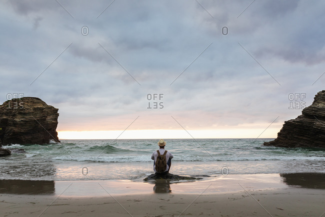 Back view of anonymous male traveler sitting on a rock at sandy coast enjoying views during summer vacation near sea at sunset