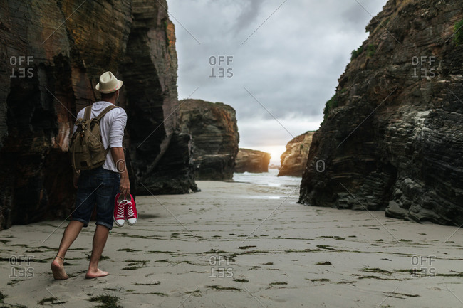 Back view of anonymous male backpacker with sneakers in hand walking alone on sandy beach near sea and admiring sunset while relaxing after hiking in nature