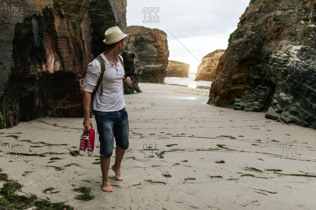 Barefooted male backpacker with sneakers in hand walking alone on sandy beach near sea and admiring sunset while relaxing after hiking in nature