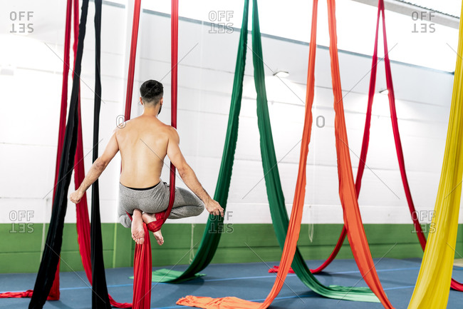Muscular bearded guy hanging on pieces of cloth and meditating while practicing aerial dance in studio