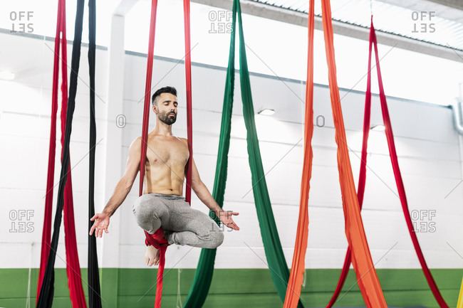 Muscular bearded guy with closed eyes hanging on pieces of cloth and meditating while practicing aerial dance in studio