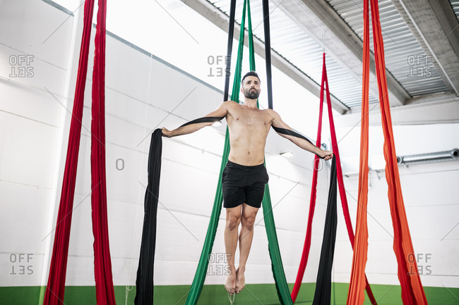 From below barefoot bearded man balancing on pieces of fabric and looking away against ceiling while practicing aerial dance in studio