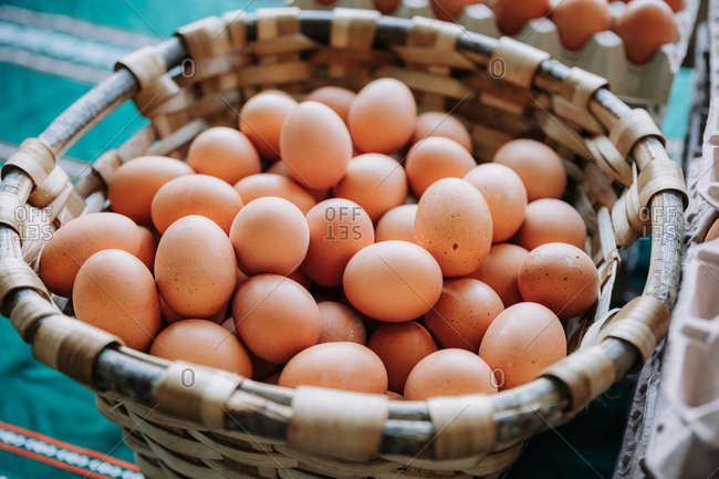Wicker basket full of brown organic eggs placed on counter on local food market