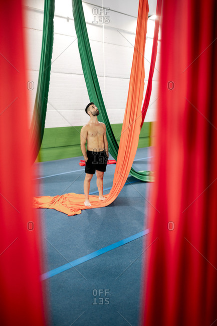 Full body shirtless male gymnast with hands in pockets looking at colorful ribbons during aerial dance rehearsal in spacious studio
