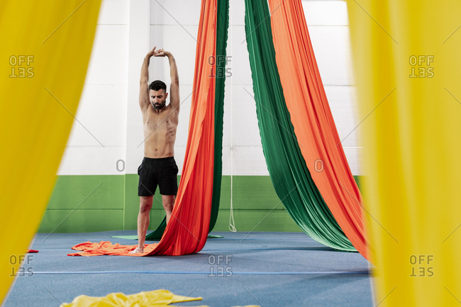 Full body muscular man raising arms over head and stretching near colorful pieces of cloth during aerial dance rehearsal in studio