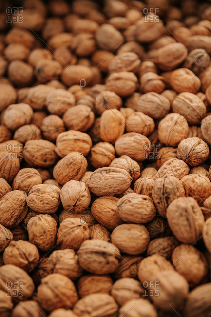 Closeup of scattered pile of natural unpeeled brown walnuts for food and cooking concept background