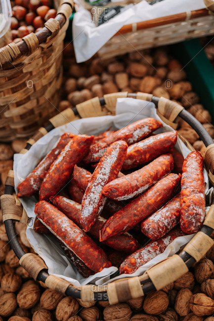 From above of whicker basket with yummy appetizing chorizo sausages placed among containers with nuts on local agricultural market