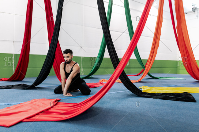Adult man in leotard kneeling on floor near colorful pieces of fabric and stretching arms while practicing aerial dance