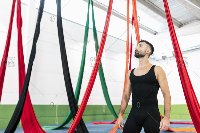Full body male gymnast looking at colorful ribbons during aerial dance rehearsal in spacious studio