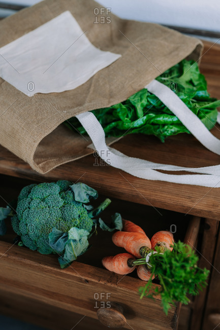 Paper bag with green leaves placed on wooden counter with fresh broccoli and bunch of carrots from farm market