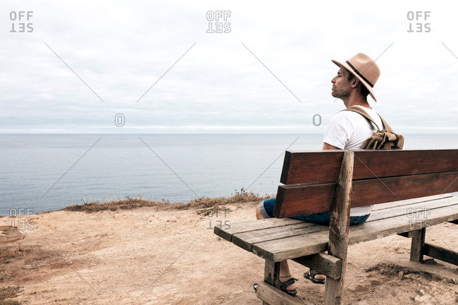 Side view high angle of male explorer in hat sitting on wooden bench and admiring spectacular scenery of sea and rocks