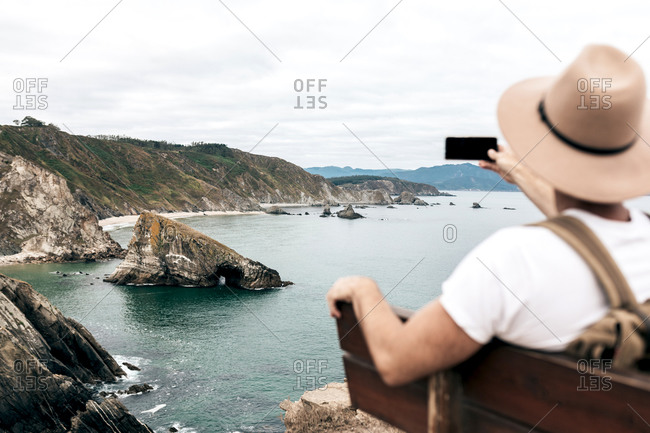 Back view of male tourist sitting on bench and taking picture of amazing cliff and sea while enjoying travel and using smartphone
