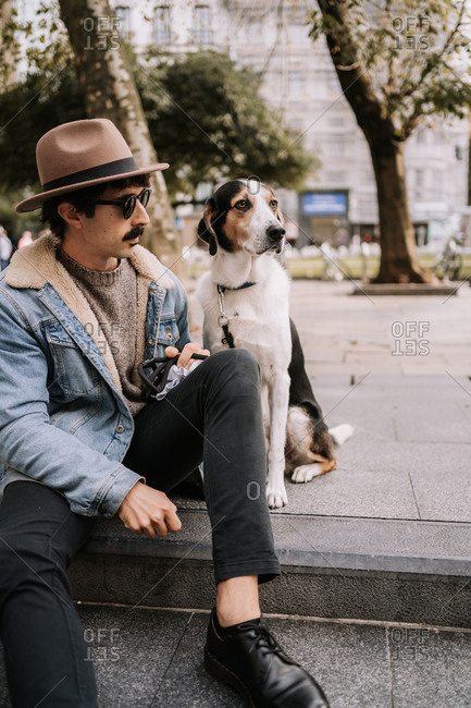 Trendy male owner sitting on pavement with obedient Treeing Walker Coonhound dog during city stroll and looking away