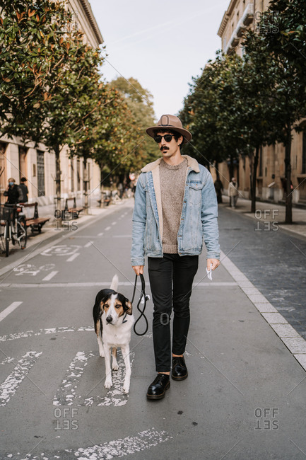Confident stylish male walking with Treeing Walker Coonhound dog along street and enjoying stroll