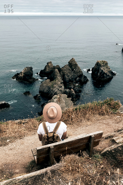 Back view high angle of male explorer in hat sitting on wooden bench and admiring spectacular scenery of sea and rocks