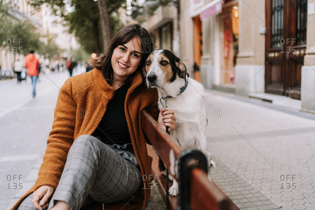 Cheerful female sitting on wooden bench with friendly Treeing Walker Coonhound dog on leash and looking at camera