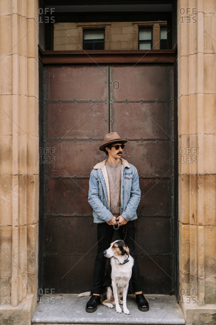 Male in trendy outfit standing near doors in city with Treeing Walker Coonhound dog on leash during city stroll