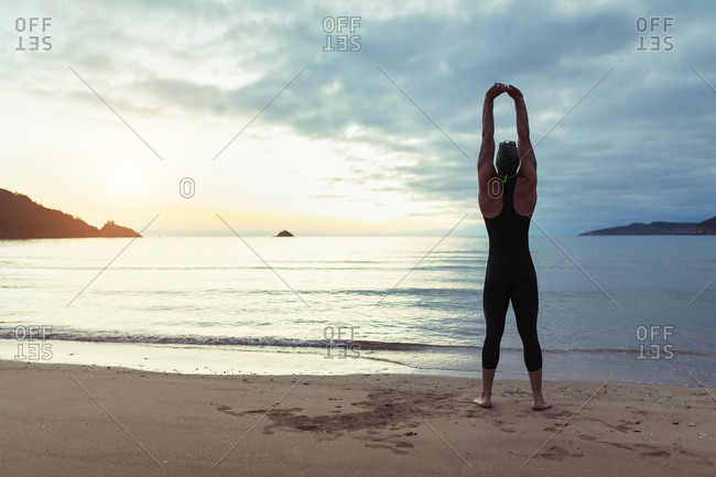 Back view of fit male swimmer in swimsuit and cap standing on seashore and stretching arms before training