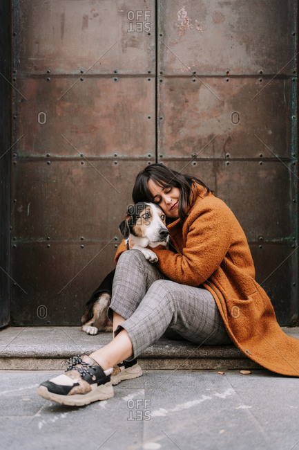 Side view of female owner gently embracing Treeing Walker Coonhound dog while sitting on street in city