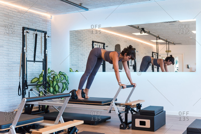 Slim adult female stretching body on modern reformer during Pilates training in gym