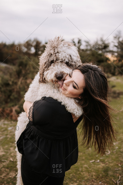 Side view of Spanish Water Dog licking face of content female while embracing in nature