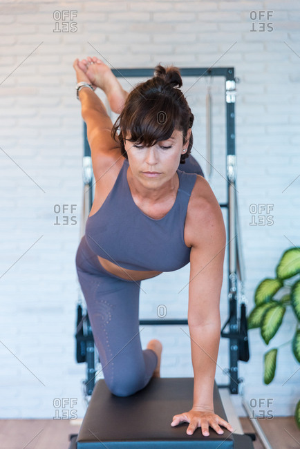 Barefoot female in sportswear doing Half Bow exercise on Pilates reformer in gym