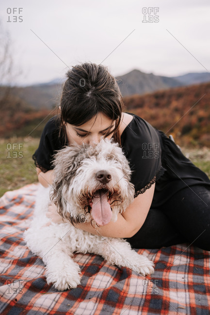 Candid female owner cuddling fluffy Spanish Water Dog while sitting on blanket in mountains and enjoying weekend together