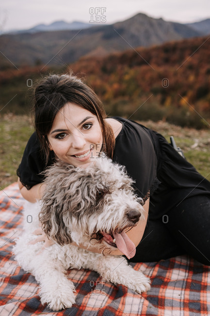 Candid female owner cuddling fluffy Spanish Water Dog while sitting on blanket in mountains and enjoying weekend together looking at camera