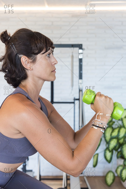 Close up view of female stretching out arms with dumbbells while standing on reformer during Pilates workout in gym