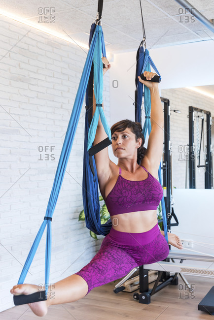 Slim woman doing splits with raised arms on aerial silks while practicing Pilates against brick wall in gym
