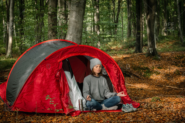 Tranquil female traveler sitting in Lotus pose near camping tent and meditating with closed eyes in woods