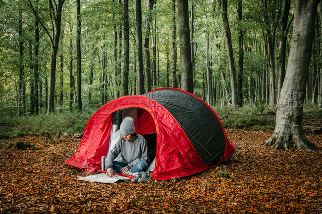 Traveling female sitting near camping tent and navigating with paper map while searching for trail during vacation in forest