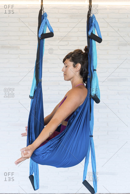 Side view of adult female with closed eyes sitting in hammock in Lotus pose and meditating while practicing aerial yoga against brick wall