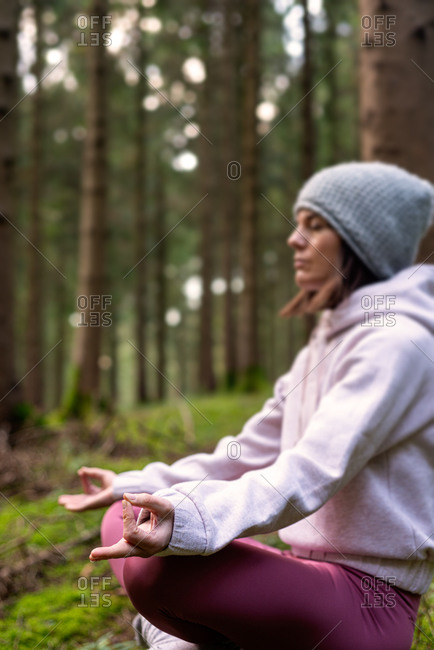 Side view of slim female traveler sitting on tree stump in Lotus pose and doing yoga with closed eyes while enjoying woods