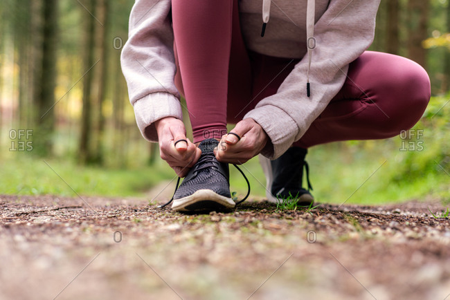Cropped unrecognizable portswoman in activewear tying shoelaces on sneakers during workout in woods while having break on path