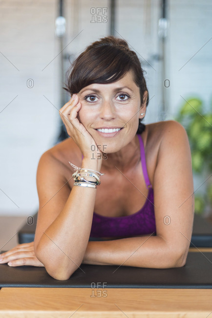 Cheerful adult female smiling and looking at camera while leaning on floor during break in aerial yoga lesson