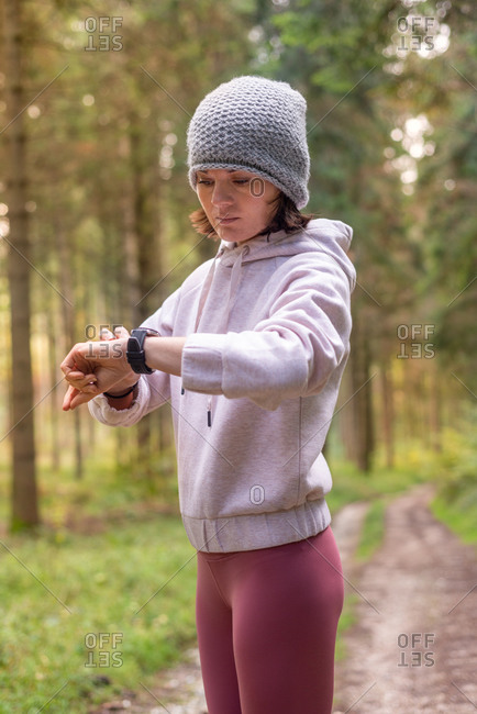 Side view of focused female runner in sportswear checking pulse on fitness tracker during cardio workout in woods