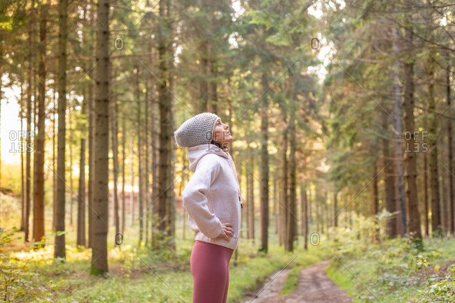 Side view of serene female traveler standing in woods enjoying early morning during adventure looking up
