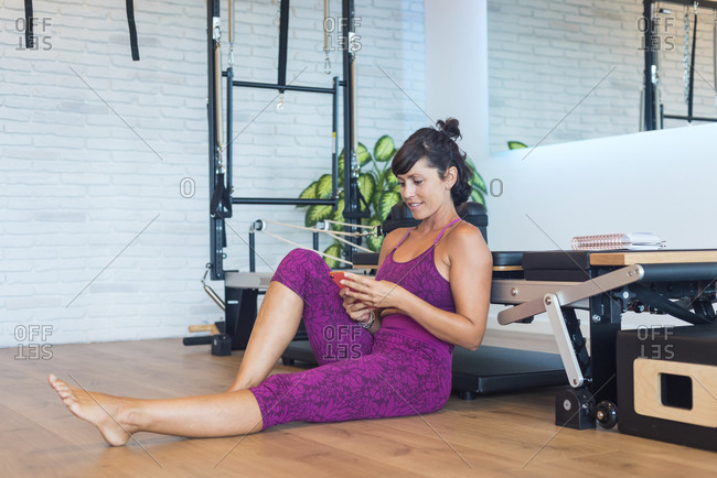 Happy female instructor sitting near Pilates reformer and dialing phone number from notebook on smartphone in gym