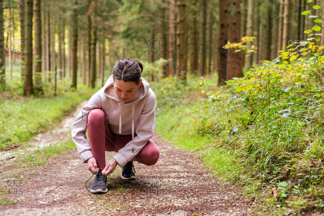 Sportswoman in activewear tying shoelaces on sneakers during workout in woods while having break on path