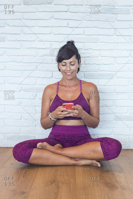 Positive adult female with drink to go smiling and browsing smartphone while leaning on brick wall sitting during break in yoga lesson