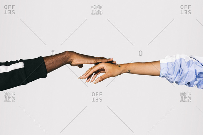 Close-up of a man's black hand on a woman's white hand over white background
