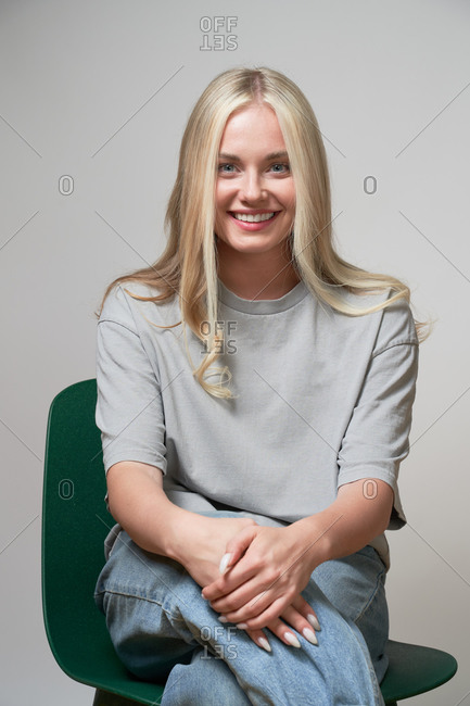 Cheerful blonde female in casual apparel sitting in studio and laughing sincerely while looking at camera
