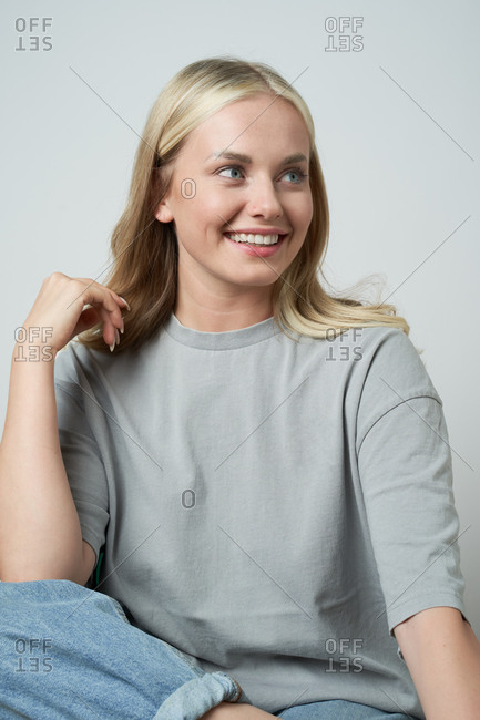 Cheerful blonde female in casual apparel sitting in studio and laughing sincerely while looking away