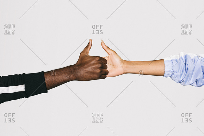 Close-up of a black man's hand holding a white woman's hand over white background