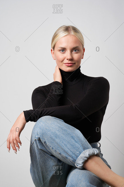 Blonde female in casual apparel sitting in chair in studio looking at camera