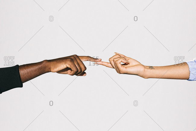 Close-up of a black man' touching white woman's finger over white background